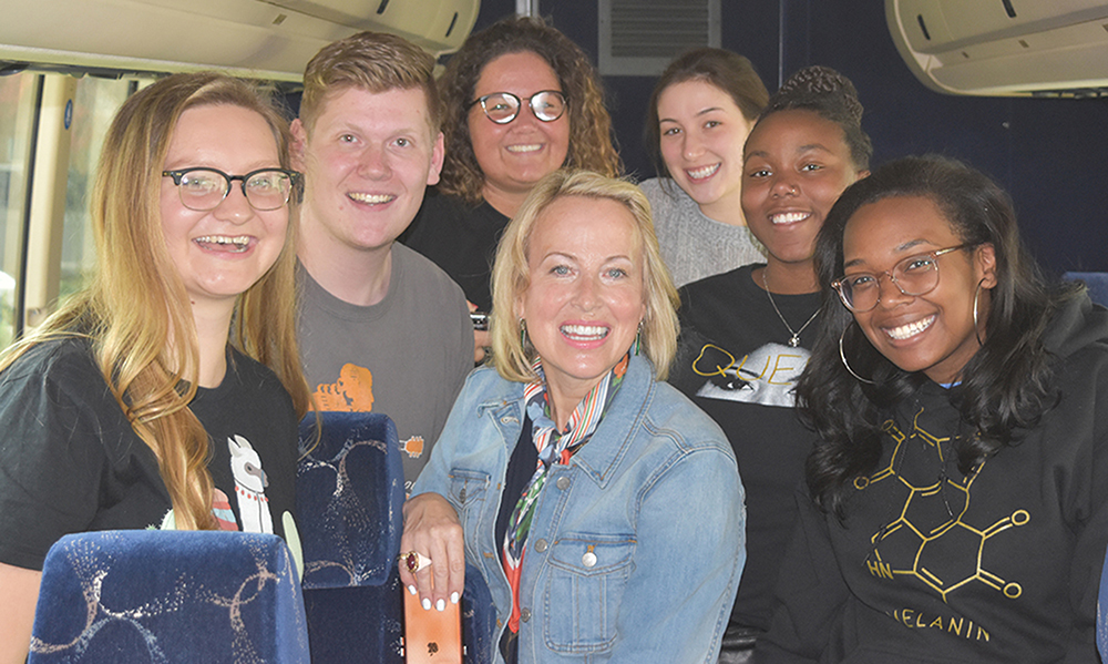 Professor Kim Denton with a group of six undergraduate students on a bus.